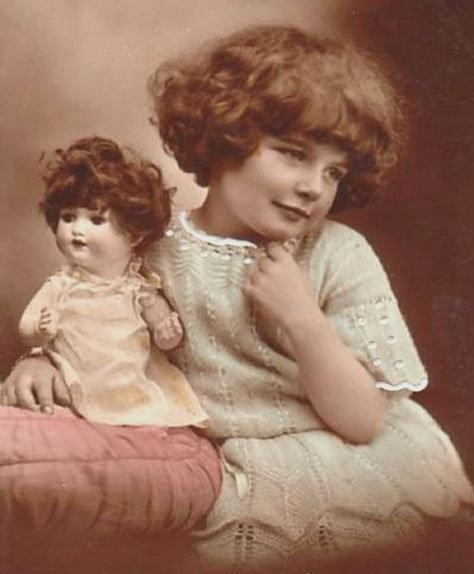 Un'immagine d'archivio che mostra una bambina e la sua bambola appartenenti a un passato remoto.
